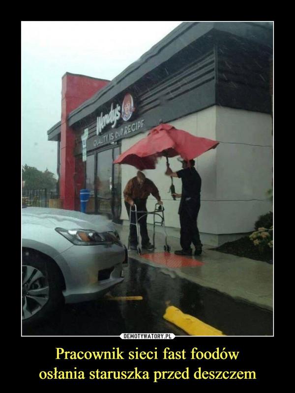Pracownik sieci fast foodówosłania staruszka przed deszczem –